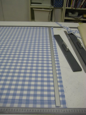 Checked fabric being straigtened in workshop